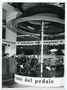Arrigo Castellani, [Sig. Pozzo] e alcuni visitatori osservano delle biciclette storiche in esposizione
