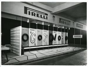 Veduta di una parete allestita con esposizione di pneumatici e cinghie di trasmissione Pirelli.