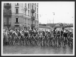 La partenza: il mossiere, Arturo Pozzo sta dando inizio alla corsa. La fotografia è eseguita a Milano e riprende viale Monza all'angolo con via Valtorta, gli edifici ripresi in fotografia oggi non sono più presenti