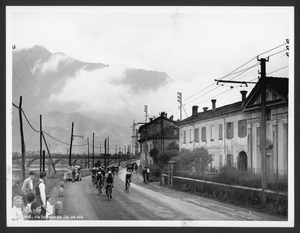 Il passaggio dei corridori a Malgrate (LC): sullo sfondo è visibile il ponte Ponte Azzone Visconti