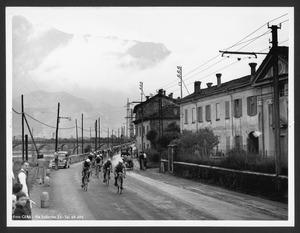 Il passaggio dei corridori a Malgrate (LC): sullo sfondo è visibile il Ponte Azzone Visconti
