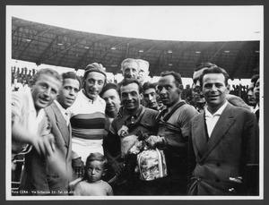 Il vincitore Alfo Ferrari insieme ad altre persone, tra cui è riconoscibile il campione del ciclismo Fausto Coppi, presente al Vigorelli per partecipare a una corsa su pista programmata all'interno di una riunione ciclistica