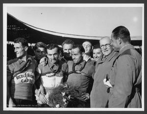 Il vincitore Alfo Ferrari al Velodromo Vigorelli, insieme ad altre persone, tra cui sono riconoscibili: Alfredo Binda, Arturo Pozzo, il corridore Arrigo Padovan, della Nicolò Biondo di Carpi, secondo classificato, e il corridore Luigi Spotti