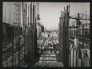Una fase della costruzione della Nuova Sede: preparazione del banchinaggio della soletta del pavimento del 5° piano. In primo piano, i ferri verticali che costituiscono l'armatura di uno dei pilastri dell'edificio. L'immagine è stata pubblicata da Fatti e Notizie (anno VIII, n. 4-5, aprile-maggio 1957, p. 11)