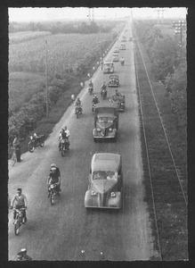 Il passaggio di auto, moto e corridori lungo una strada di campagna