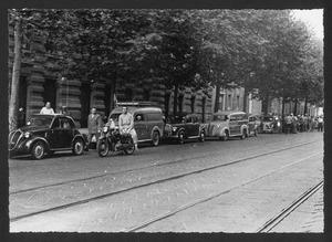 Una moto e un furgoncino con la scritta Pirelli, in sosta lungo un viale alberato