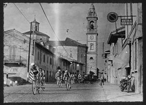 Il passaggio dei corridori nel comune di Gorgonzola (MI): la fotografia, eseguita in via Serbelloni, ritrae il campanile e parte della Chiesa dei SS. Protaso e Gervaso