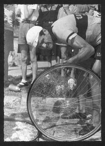Un corridore controlla lo pneumatico della bicicletta