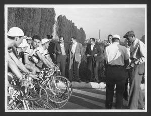 I corridori e altre persone, organizzatori e membri della giuria, prima dell'inizio della corsa, in viale Palmanova a Milano: il mossiere è Luigi Borsano