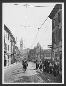 Il passaggio dei corridori nel comune di Gorgonzola (MI): la fotografia è eseguita in via Italia e sullo sfondo è visibile la Chiesa dei SS. Protaso e Gervaso