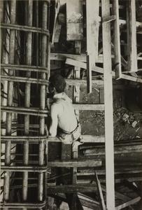 Veduta dall'alto di un operaio edile al lavoro sull'intelaiatura in metallo