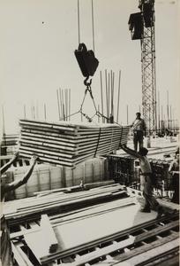 Veduta del cantiere del Centro Pirelli con operai edili: posa di lastre in legno attraverso la gru