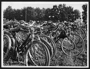 Numerose biciclette e alcune persone in un campo