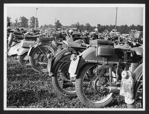 Alcune motociclette in un parco: le persone presenti, in piedi su autobus e furgoni, sono forse spettatori di una corsa