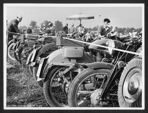 Alcune motociclette in un parco, dove sono presenti anche alcune persone, forse spettatori di una corsa