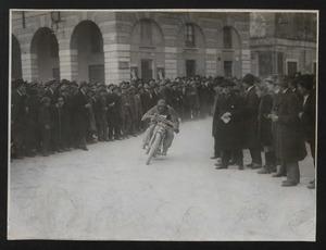 Un momento di una corsa motociclistica: il passaggio di un pilota in una piazza tra due ali di pubblico