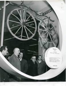 Il ministro On. Armando Angelini con Arrigo Castellani in visita allo stand Pirelli. Esposizione della Draisina a pedali del 1855.