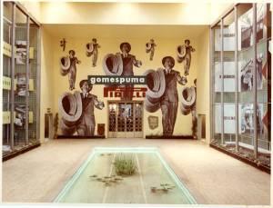 Veduta centrale dello stand Pirelli. Alle pareti teche espositive. Al centro una piccola piscina. Sul fondo una pubblicità di Federico Scopinich.
