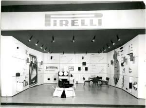 Veduta frontale dello stand Pirelli per Articoli Vari. Alle pareti esposizioni di oggetti accessori  per automobili. Al centro una macchina dimostrativa per sospensioni.