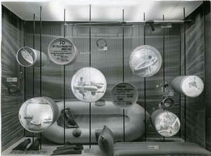 Moroni Gomma display cabinet set up with underwater fishing items: mattresses, mask, flippers, dinghies.