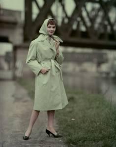 Modella ritratta sull'argine del Naviglio Grande a Milano con l'impermeabile Pirelli D 1495 in levantina di cotone verde smeraldo, con manica a giro, collo aperto, impunture, spacco dietro e cintura da annodare