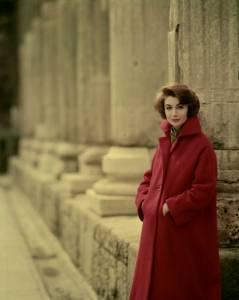 Modella ritratta accanto alle Colonne di San Lorenzo a Milano con il soprabito D 1555  in lana mouflon rosso porpora, con maniche a chimono, finte tasche al petto e tasche tagliate profonde