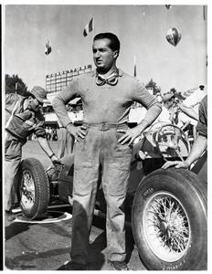 Un ritratto a figura intera del pilota Alberto Ascari accanto alla sua auto gommata con pneumatici Pirelli Corsa